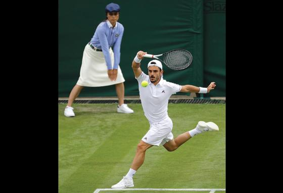 "The line judge signals ""in,"" so Italy's Thomas Fabbiano plays the ball at the 2019 Wimbledon Tennis Championships. (AP)"