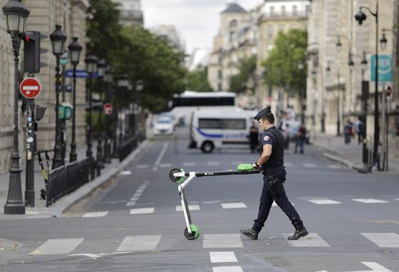 Police officers have to remove electric scooters from walkways and streets around Notre Dame cathedral in Paris, France. People tend to leave them wherever they are when they finish riding. (AP)