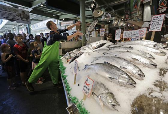Kids visit the Pike Place Fish Market in Seattle, Washington. They are amused by workers flinging and catching huge salmon. (AP)
