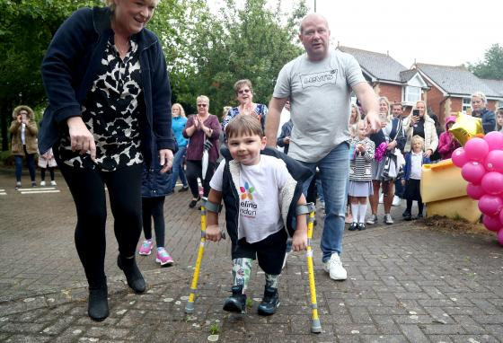 Tony Hudgell, who uses prosthetic legs, finishes his fundraising walk with his parents. (Gareth Fuller/PA Wire/AP)