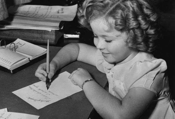 Eight-year-old movie star Shirley Temple writes a letter at her home in California in December  1936. (AP)