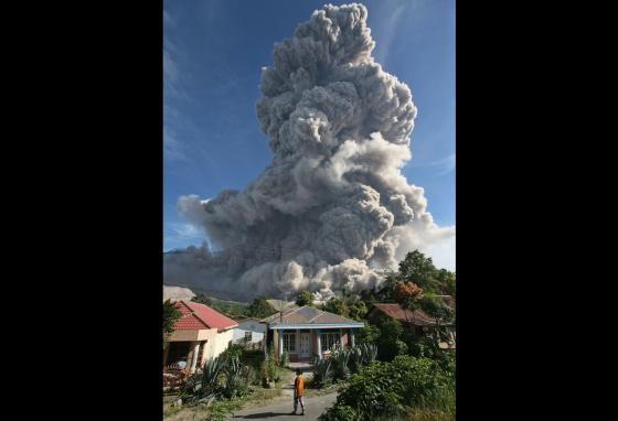 A villager stands outside her house as Mount Sinabung releases ash in Gamber, North Sumatra, Indonesia. Indonesia has the most active volcanoes in the world. (AP)