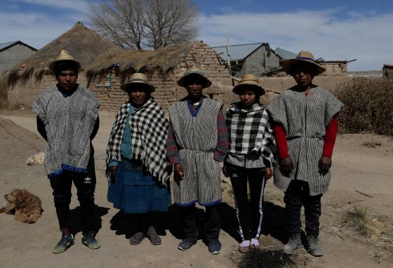 Members of the Choque family, from left, Jose, Evarista Flores, Rufino, Abelina, and Abdon, pose for a photo. With no land for farming, the young men take jobs in other towns. (AP/Juan Karita)