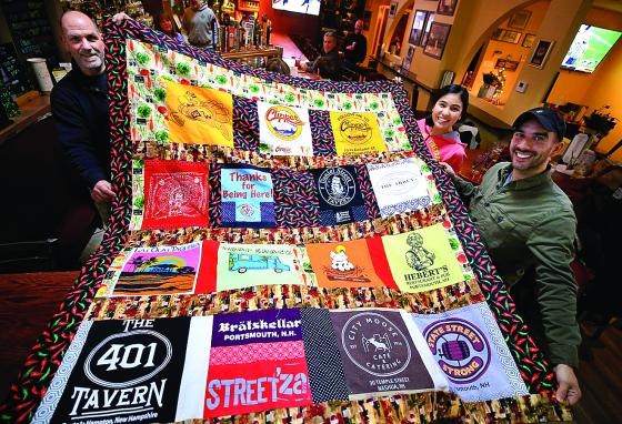 Rick Miller and Hajer and Nick Arriaga hold up a quilt made from T-shirts from local restaurants around Portsmouth, New Hampshire. (Ioanna Raptis/Portsmouth Herald via AP)