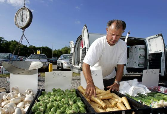 Frank Betti arranges parsnips at his produce stand in South Amherst, Ohio. (AP/Mark Duncan)