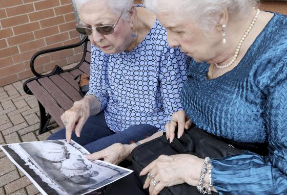 Jean Harrison, left, and Jane Umbarger look at a photo of themselves as babies. (Matthew Apgar/Northwest Herald/AP)