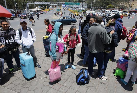 Ms. Cadiz and Angelis (center) traveled through four countries. Here, they wait with other migrants for hours before passing into Ecuador. (AP)